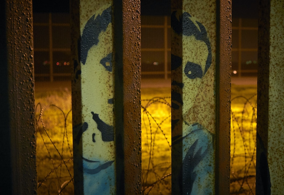 An image of a boy is painted on the bars of the border wall, in front of coils of razor wire, seen from Tijuana, Mexico. President Trump's proposal to end the partial government shutdown includes funding for more border wall, but also provisions that further restrict asylum seekers.