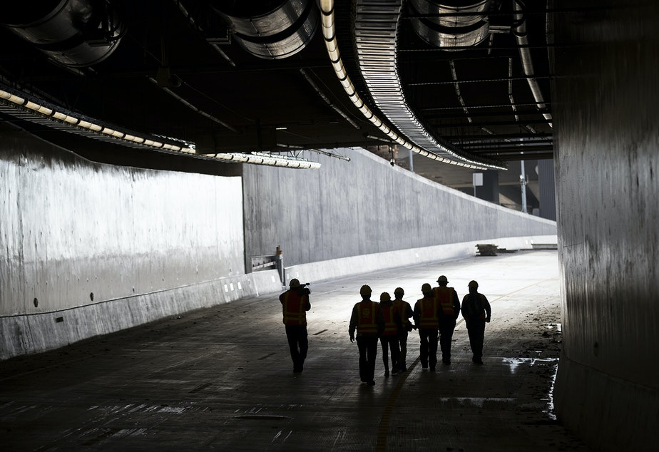 caption: Members of the media walk in the southbound lane on Thursday, November 15, 2018, inside the State Route 99 tunnel in Seattle.