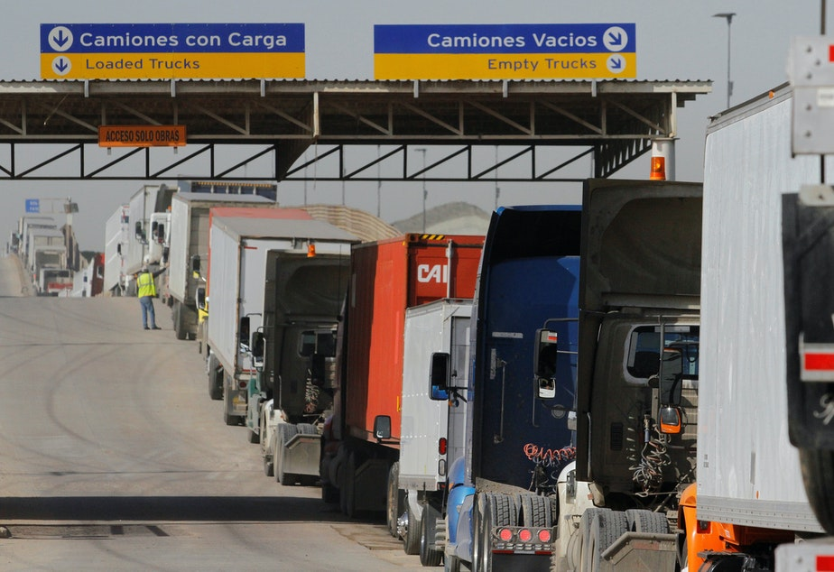 caption: Trucks wait to enter the United States at the border crossing in Tijuana, Mexico, in 2017. More than $1.6 billion in goods flow across the border each day.