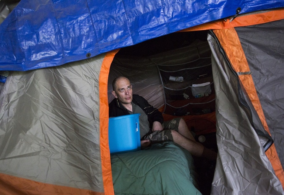 caption: Kevin Boggs in his tent in the Jungle, before the tent encampment was torn down in 2016. Boggs was signed up at methadone clinics because of an addiction.