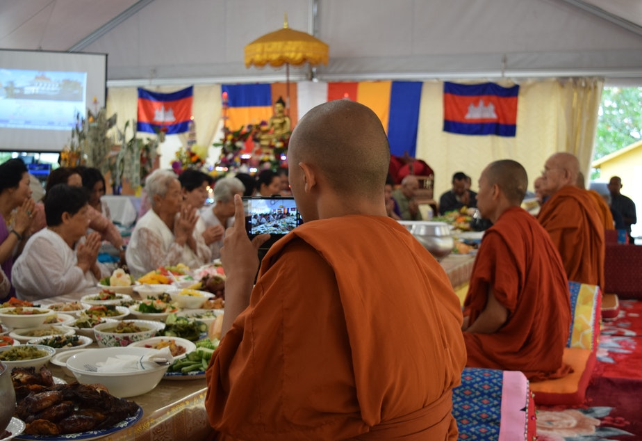 caption: Venerable Prenz Sa-Ngoun snaps photos of a Sunday Buddhist ceremony on his phone. He later posts his photos on Instagram.