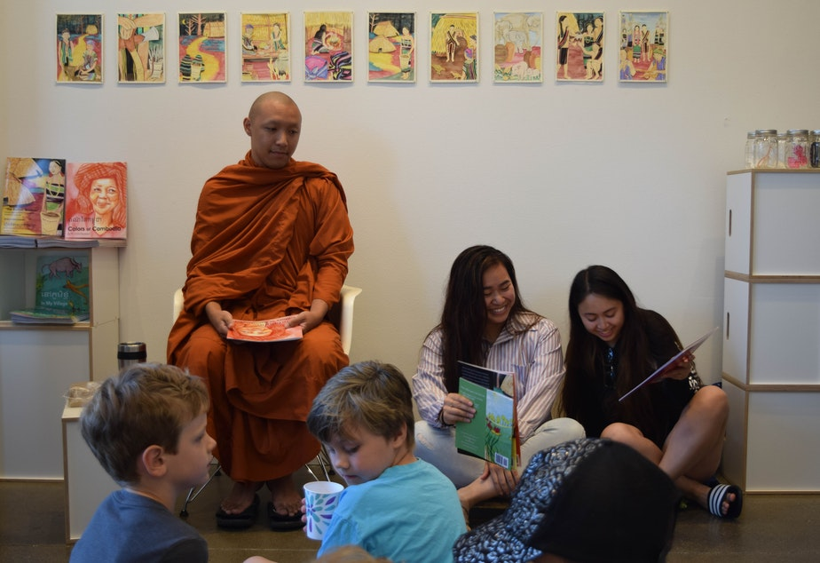 """caption: Venerable Prenz and two members of the University of Washington Khmer Student Association, Melissa Ouk and Molica Perry, prepare for a bilingual book reading of """"Colors of Cambodia"""" in Khmer and English."""